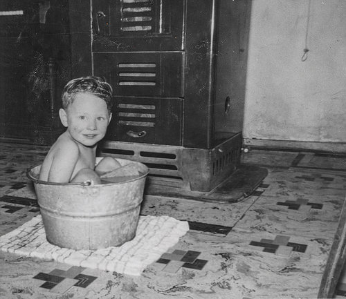 Small boy sitting naked in tin bath