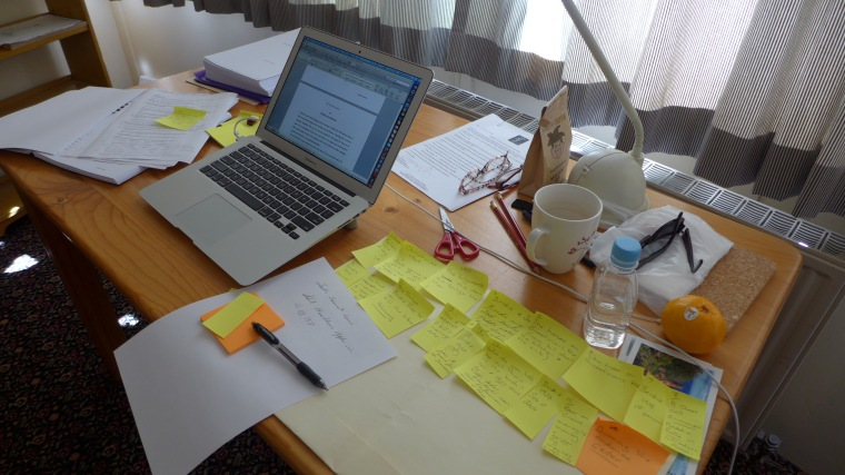 picture of a writer's desk with notes and laptop
